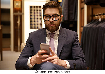 Serious man in suit and eyeglasses holding mobile phone