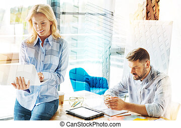 Serious man looking at the smartphone while his coworker holding a laptop
