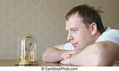 Serious man looks at the table clock with pendulum