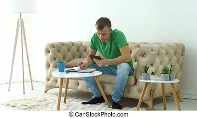Serious man on sofa with digital tablet using diary