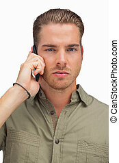 Serious man on the phone looking at camera