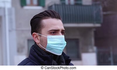 Serious young man with short haircut puts on blue protective medical mask among rotating city closeup merge video