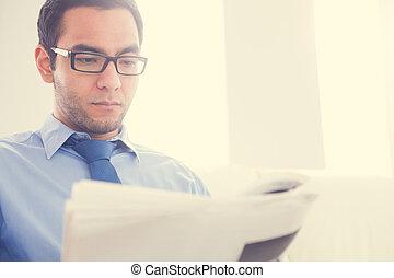 Serious man reading a newspaper