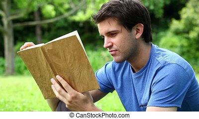 Serious man reading a novel