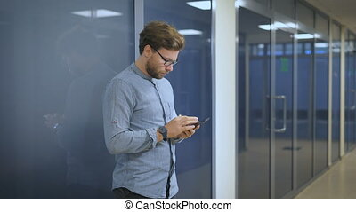 Serious man standing at the wall in an office and writing sms on mobile phone.