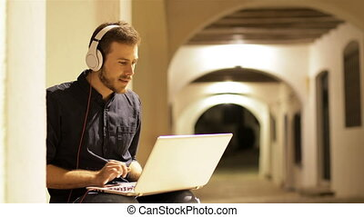Serious man using a laptop with headphones sitting in a town street in the night