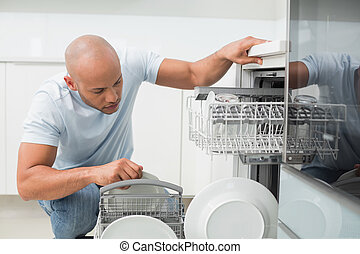 Serious man using dish washer in kitchen - Serious young man...