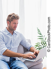 Serious man using his laptop on a couch