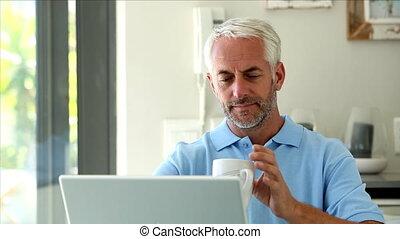 Serious man using his laptop while