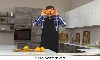 Serious man with a beard fooling around with oranges in a...
