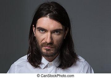 Serious man with beard and long hair looking at camera
