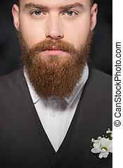 Serious man with beard looking at camera