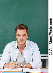 Serious Man With Folder In Front Of Chalkboard