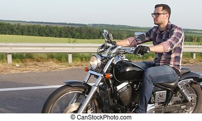 Serious man with glasses on a motorcycle. Overhead shot