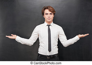 Serious man with palms up on chalkboard background