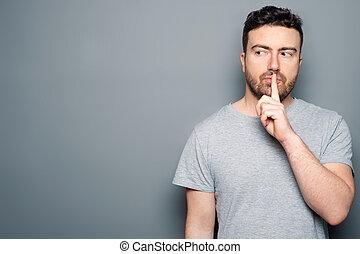 Serious man with silence symbol, studio portrait