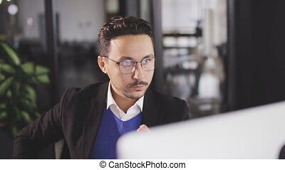 Serious man working at office on a laptop