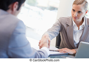 Serious manager interviewing a male applicant in her office