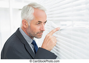Serious mature businessman peeking in office - Side view of...
