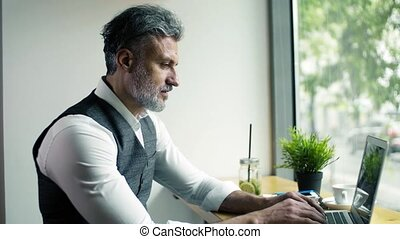 Serious mature businessman sitting at the table in a cafe, working.