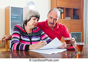 serious mature couple fills in questionnaire together