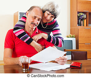 serious mature couple looking  document