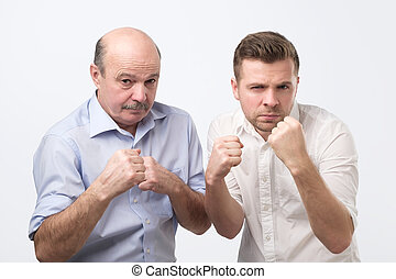 Serious mature man and his adult son keep hands in fists in protective or defensive gesture