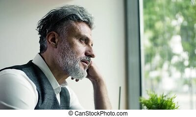 Serious mature man sitting at the table in a cafe, working.