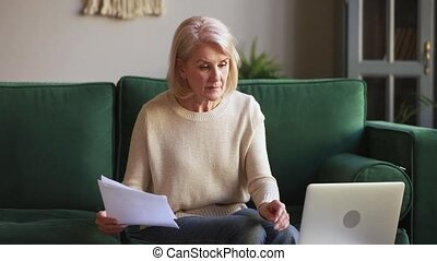 Serious mature woman calculating bills holding documents using laptop