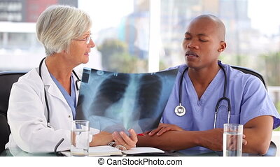 Serious medical team looking at a chest x-ray