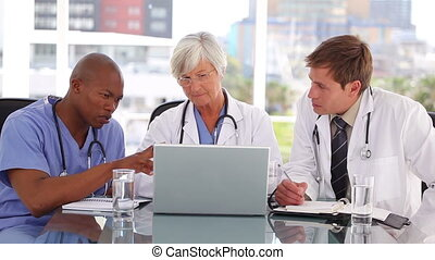 Serious medical team looking at a laptop