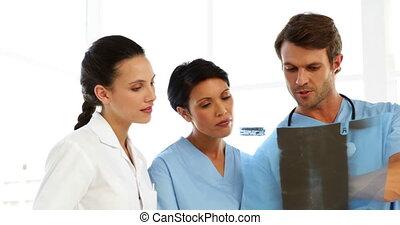 Serious medical team looking at xray