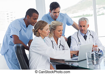 Serious medical team using a laptop
