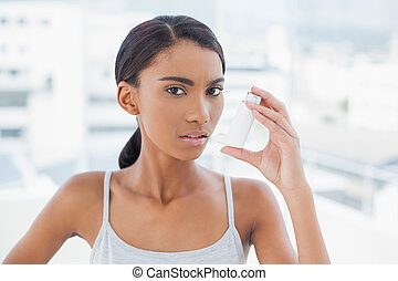 Serious model using her asthma atomizer
