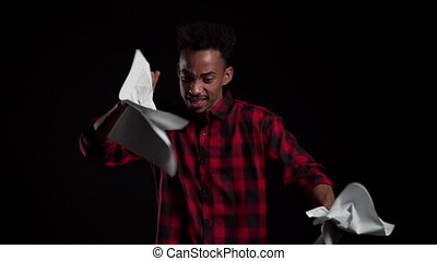 Serious modern businessman tearing contract in pieces. Angry furious male african office worker throwing crumpled paper, having nervous breakdown at work, screaming in anger, stress management.
