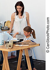 Mother and her daughter preparing paint