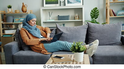 Serious Muslim woman in hijab working with laptop sitting on...