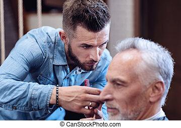 Serious nice hairdresser making a haircut