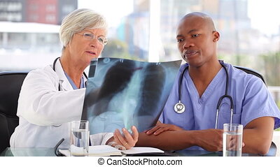 Serious nurse listening to a mature doctor