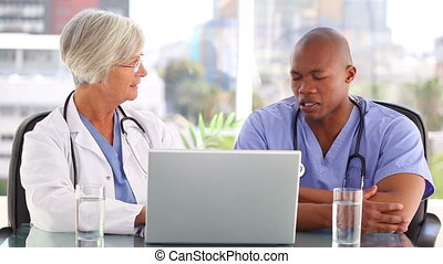 Serious nurse talking with a doctor in front of a laptop