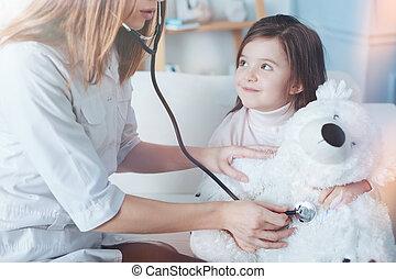 Serious nurse using stethoscope for measuring pressure