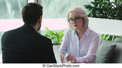 Serious middle aged old businesswoman hr manager employer listen businessman job applicant during employment interview talk to partner client discuss online project at business meeting office table