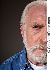 Serious old male demonstrating distrust - Half face of aging...