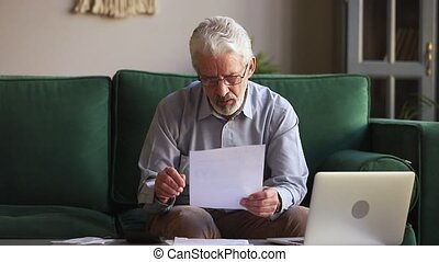 Serious old man holding paper calculating domestic bills at home