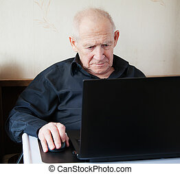 serious old man holding computer mouse - he is working on a laptop