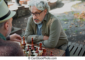Serious old men playing chess with confidence