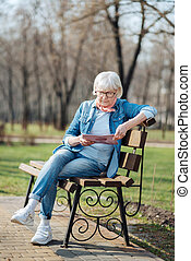 Serious old woman reading a magazine