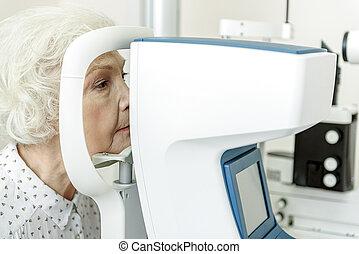 Serious old woman sitting near optical apparatus