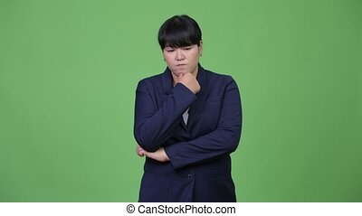 Serious overweight Asian businesswoman thinking