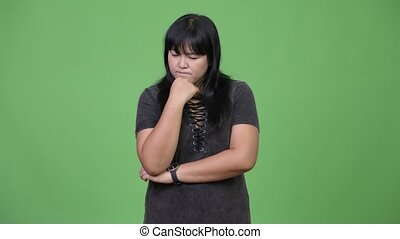 Serious overweight Asian woman thinking - Studio shot of...